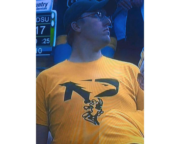 WDAY.com News - Screen Capture. A North Dakota State University supporter was spotted at a football game Nov. 5 with an obscene T-shirt, modified with the University of North Dakota's new Fighting Hawks logo altered with a single-feathered Native figure on its knees before a phallus extending from the Bison logo.