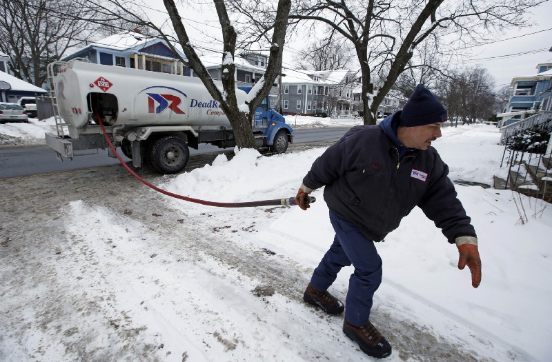 A man delivers heating oil to a house in Maine in 2015. CREDIT: AP Photo/Robert F. Bukaty.
