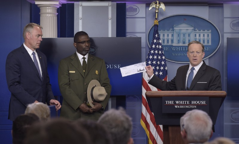 White House press secretary Sean Spicer, right, holds up a check during the daily briefing with Interior Secretary Ryan Zinke, left, and Harpers Ferry National Historic Park Superintendent Tyrone Brandyburg. CREDIT: AP Photo/Susan Walsh.