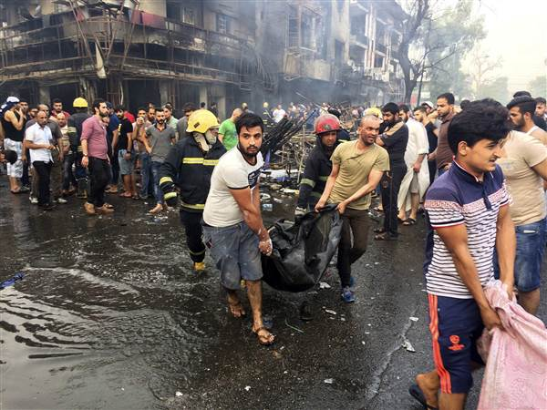 Iraqi firefighters and civilians carry bodies of victims killed in a car bomb at a commercial area in Karada neighborhood, Baghdad, Iraq on Sunday. Khalid Mohammed / AP