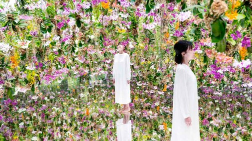 Still image taken from video of two women wakling on a mirrored floor immersed in masses of dangling orchids.
