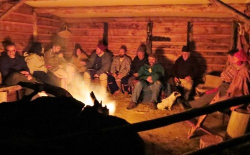 Open-faced shelter gathering lit by the fire-light.