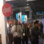 Man holding a cnet sign on a stick, guiding a group at CES