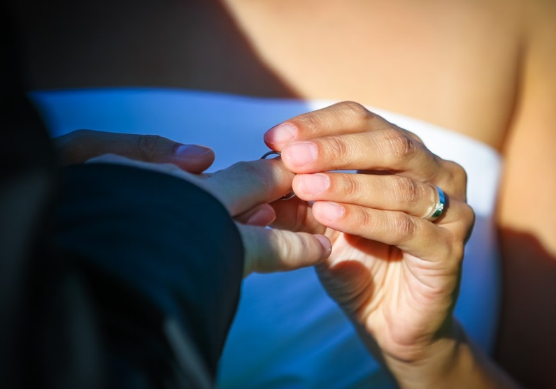 Das Foto zeigt wie die Braut dem Bräutigam den Ehering ansteckt.