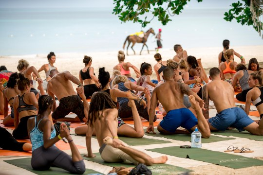 A Yoga class stretching on the beach. Photo by Corey Hamilton with a man in a pick hat leading a horse in the background by the edge of the ocean.