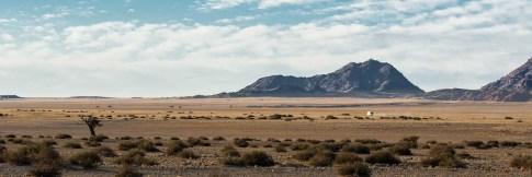 Camper fährt durch die Namib mit Bergen im Hintergrund