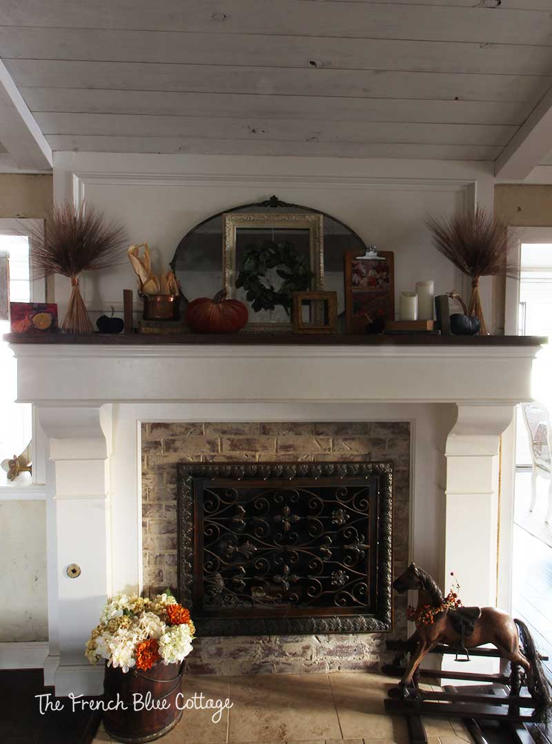 Fall fireplace mantel with wheat and velvet pumpkins.