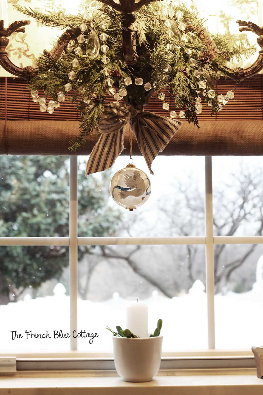 Christmas ornament hanging from the kitchen window chandelier.