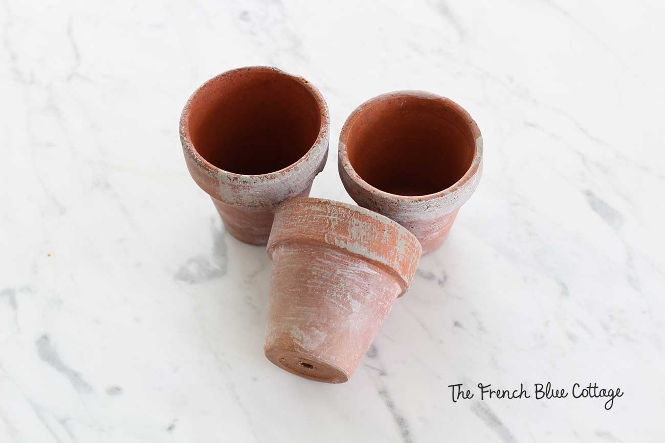 Clay pots dry brushed and whitewashed with gray paint.