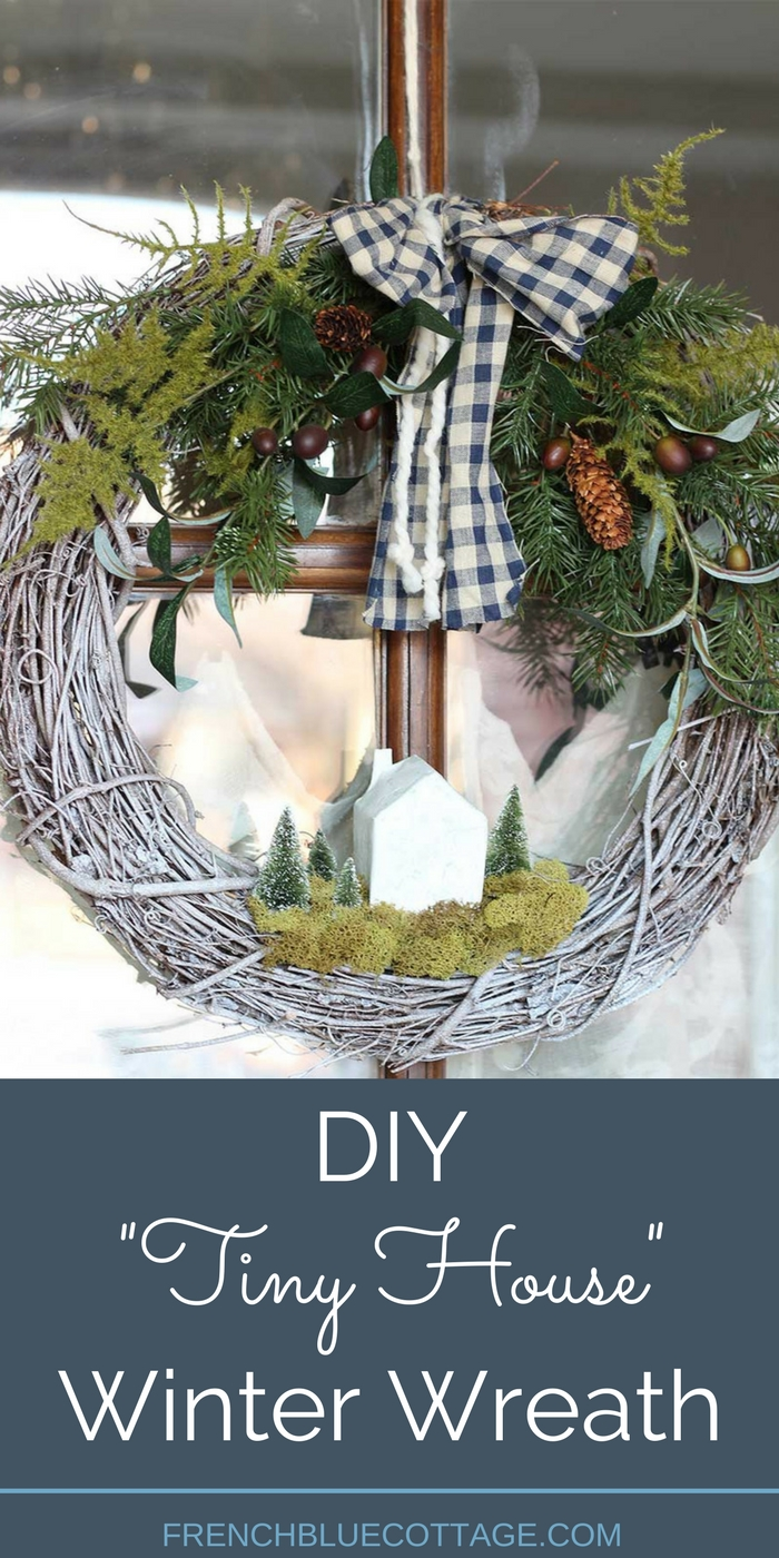 A DIY winter wreath with a paper mâché house and bottle brush trees.