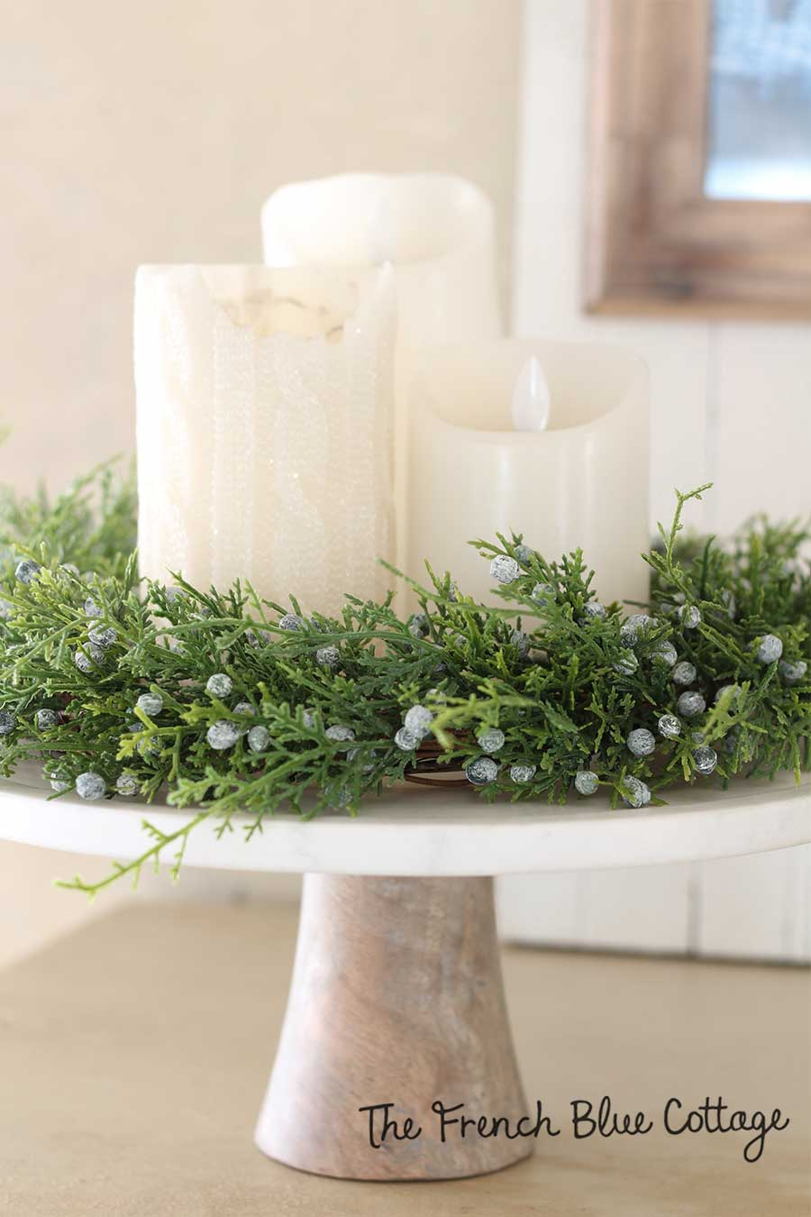 Candles on a cake stand with winter wreath.