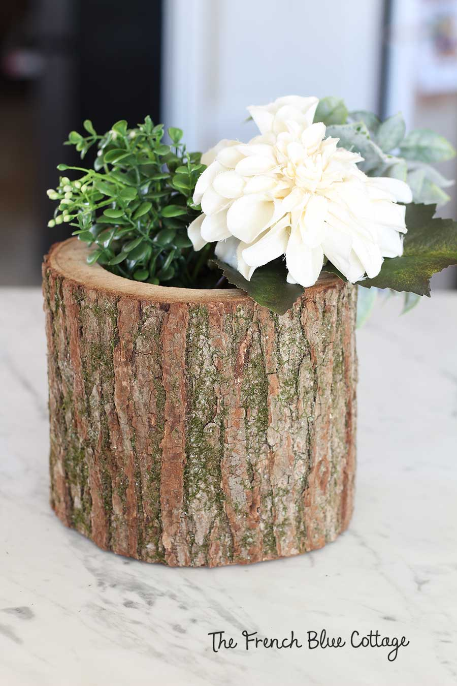 Ivory flowers and leaves in wood log vase.