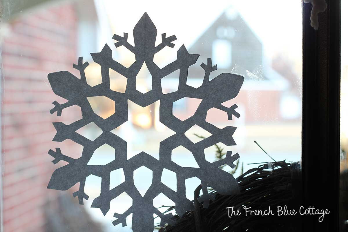 Paper snowflake cut out on window.