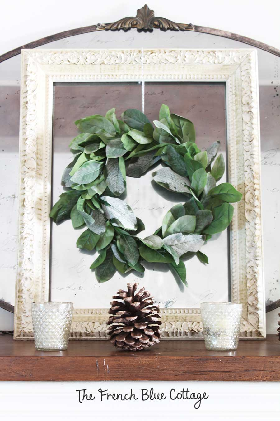 Pinecones on a winter mantel with a layered wreath, frame, and mirror.