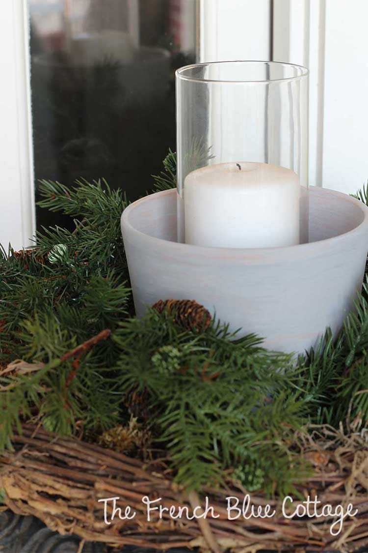 Whitewashed clay pots with candles and greenery on front porch.