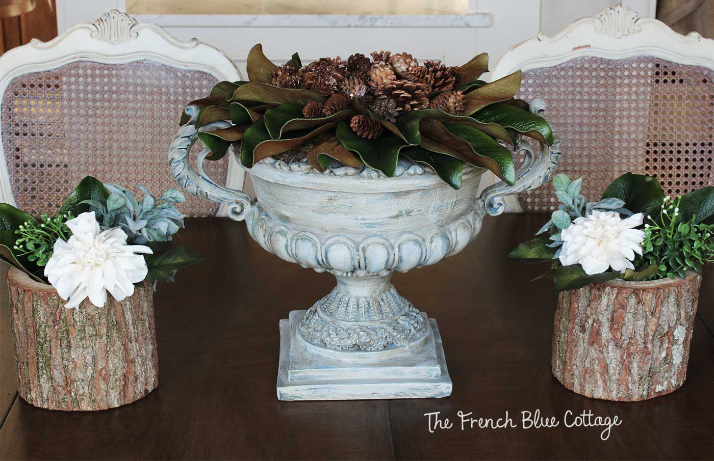 Simple winter table with magnolia, pinecones, and flowers.