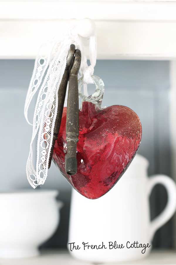 Blown glass heart with keys and lace.