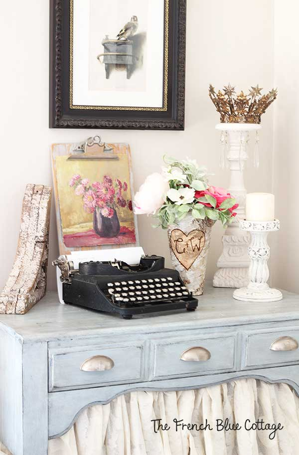 Vignette with typewriter, candle, flowers, and a painting.