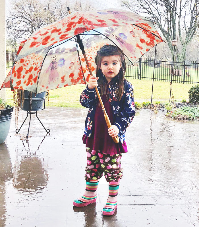 A little girl with an umbrella in the rain.