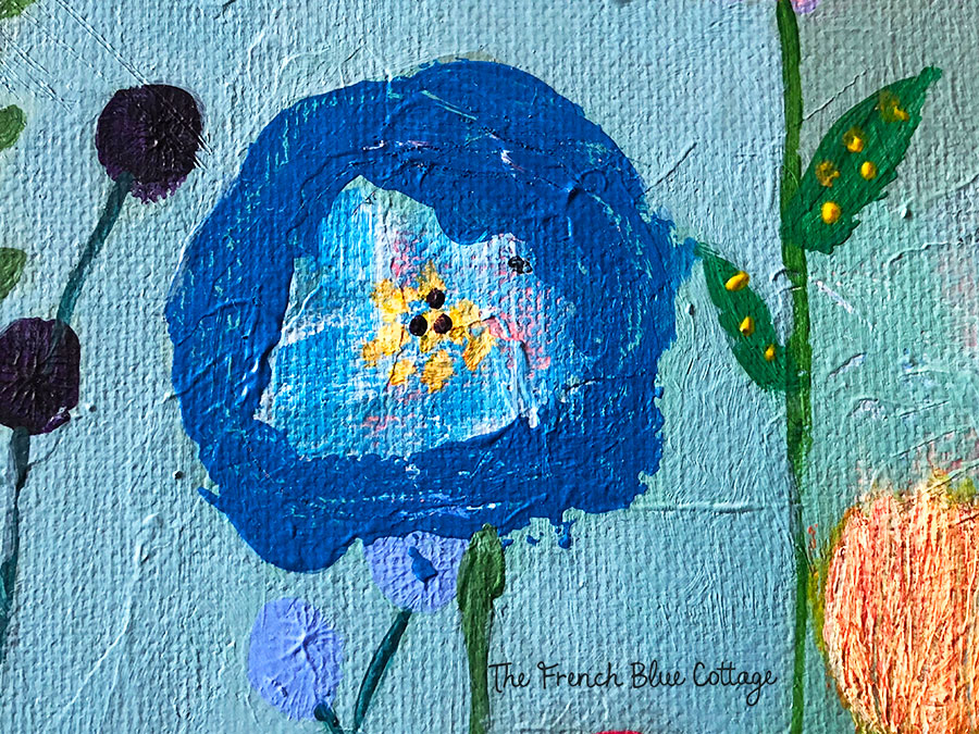 Blue flower with layered paint underneath and lots of texture.