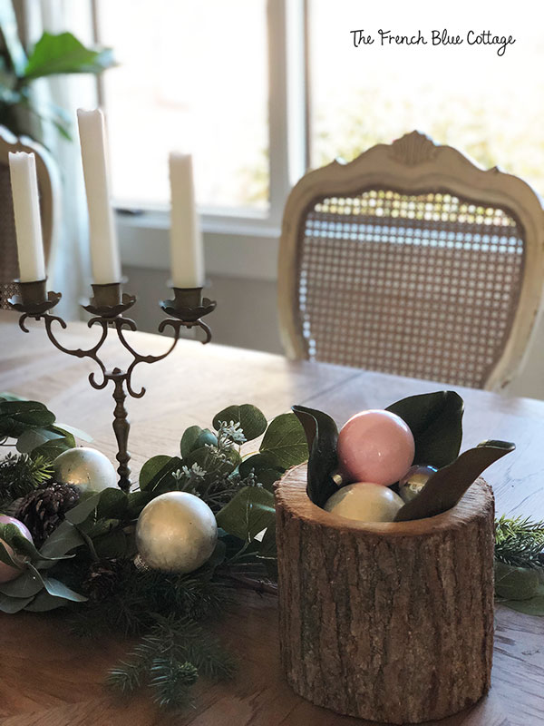 Dining room table with log centerpiece and pink ornaments.