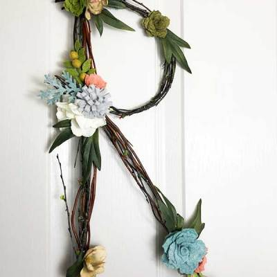 twig letter initial with felt flowers hanging on door