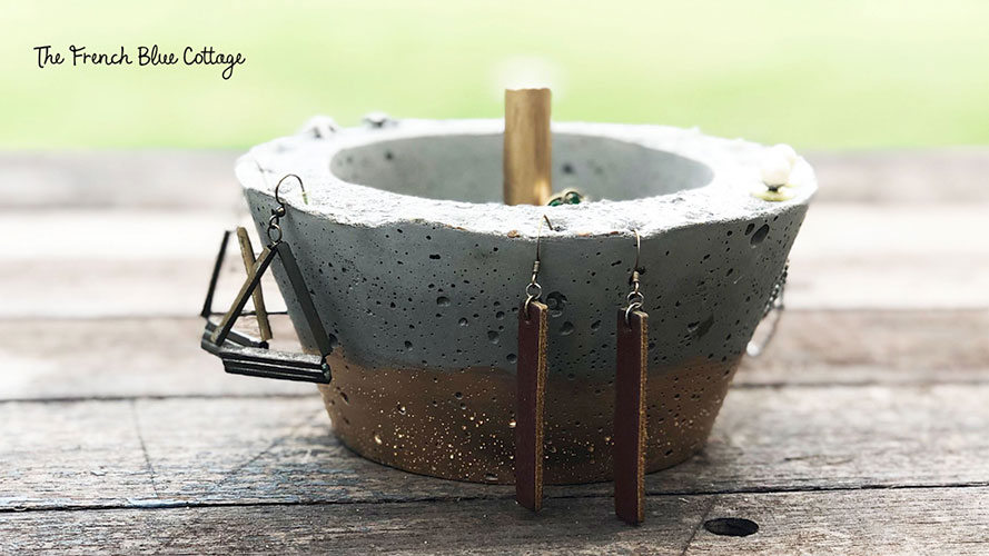 gilded concrete jewelry bowl with earrings hanging on outside