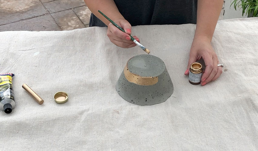 painting a concrete bowl with gold gilding liquid