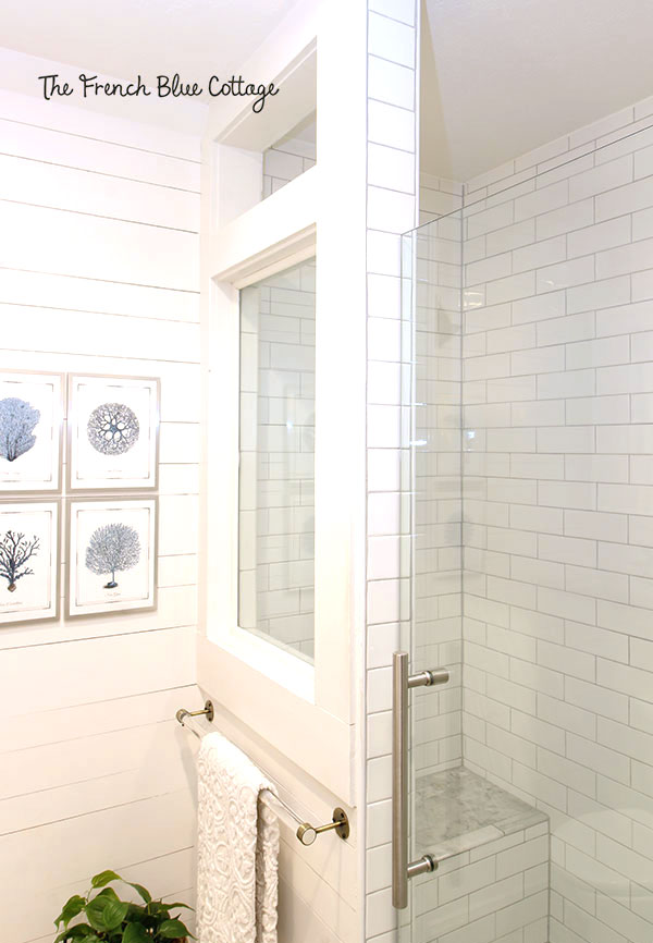 shower with a half wall with a tempered glass window