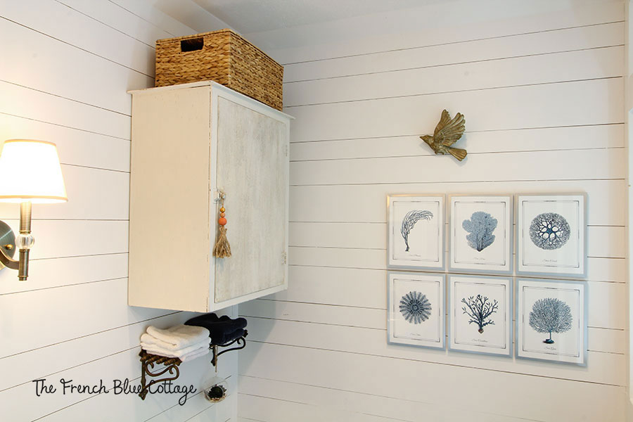 coastal farmhouse bathroom with chippy cabinet, tassel, and seagrass basket