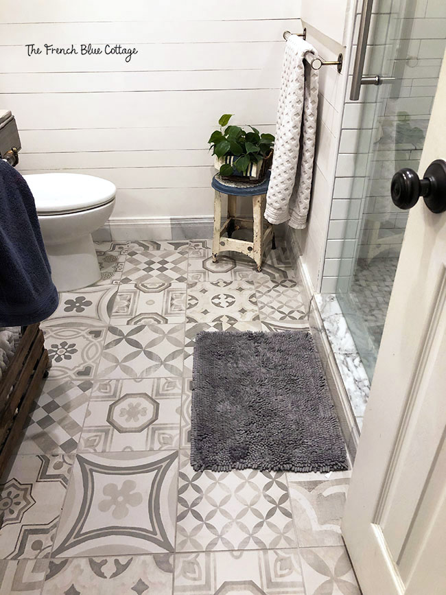 patchwork tiles in gray and white on bathroom floor
