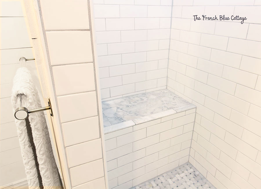 built in marble and subway tile shower bench