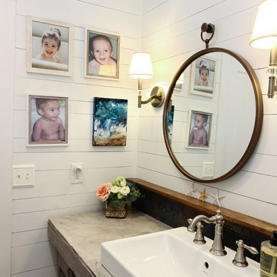 coastal farmhouse bathroom with photos of children and circle mirror