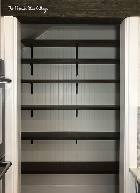 beadboard and open shelves with metal brackets in a kitchen pantry under stairs
