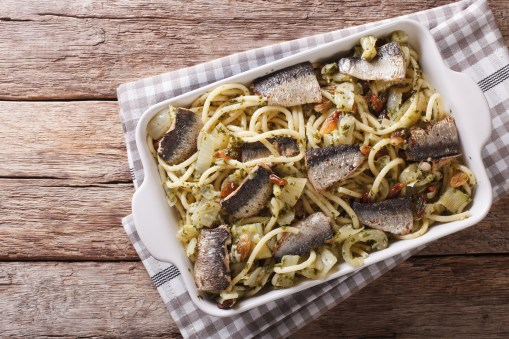 Italian food: pasta with sardines, fennel, raisins and pine nuts close up in baking dish. horizontal top view