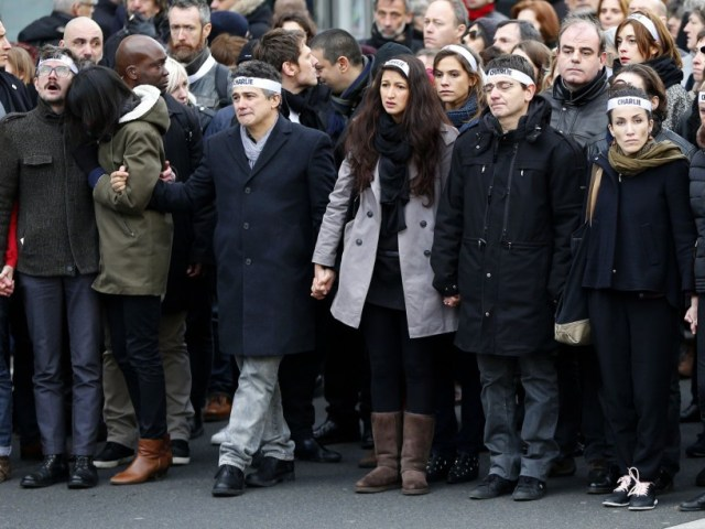 French columnist for Charlie Hebdo Patrick Pelloux (4thL) and cartoonist Luz (2ndL) take part with family members and relatives of the seventeen victims in a solidarity march in the streets of Paris