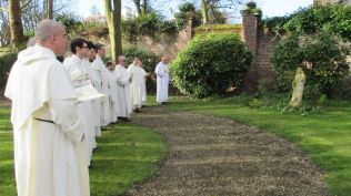 Les frères chantent la résurrection autour de la statue de la Vierge Marie dans le parc du couvent de Lille au matin de Pâques
