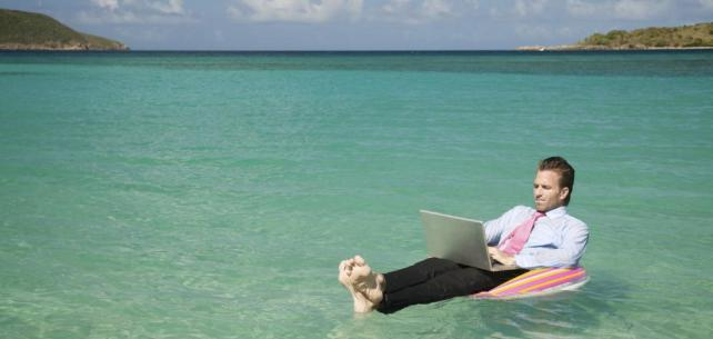 Man relaxing while working on the beach.