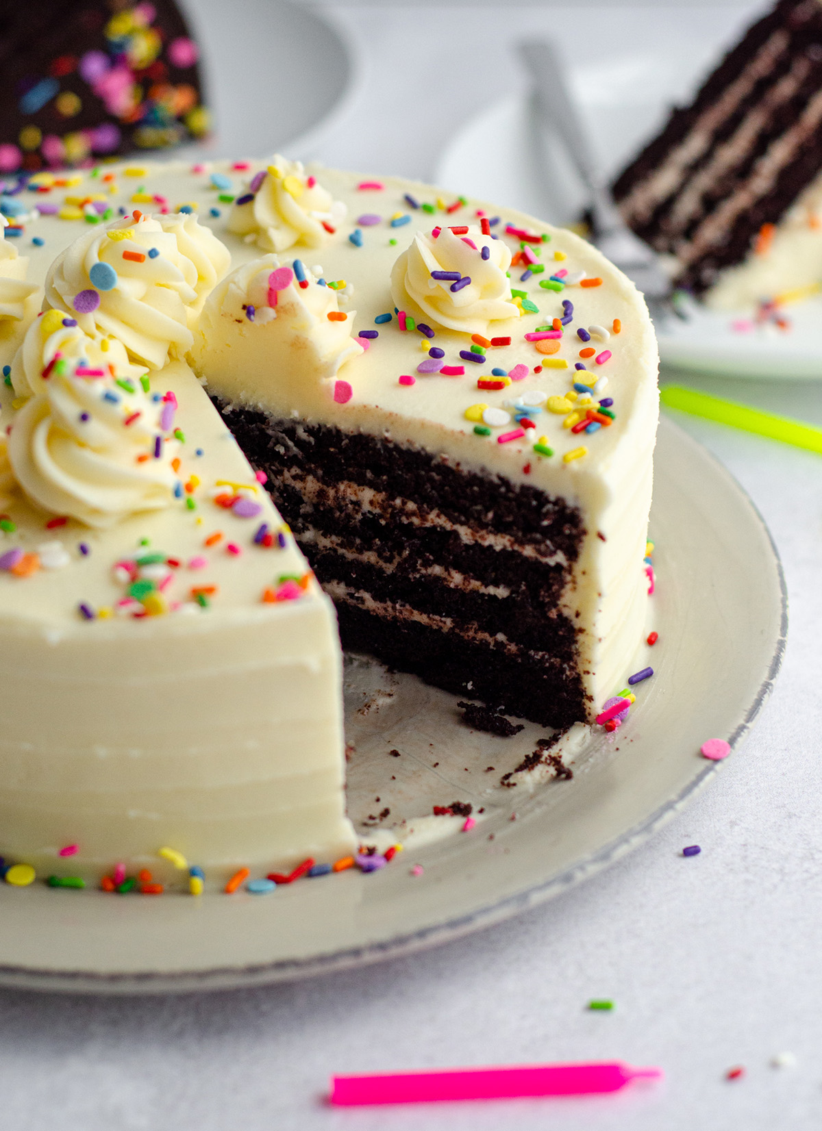 chocolate layer cake with vanilla buttercream and rainbow sprinkles on a plate with a slice taken out of it