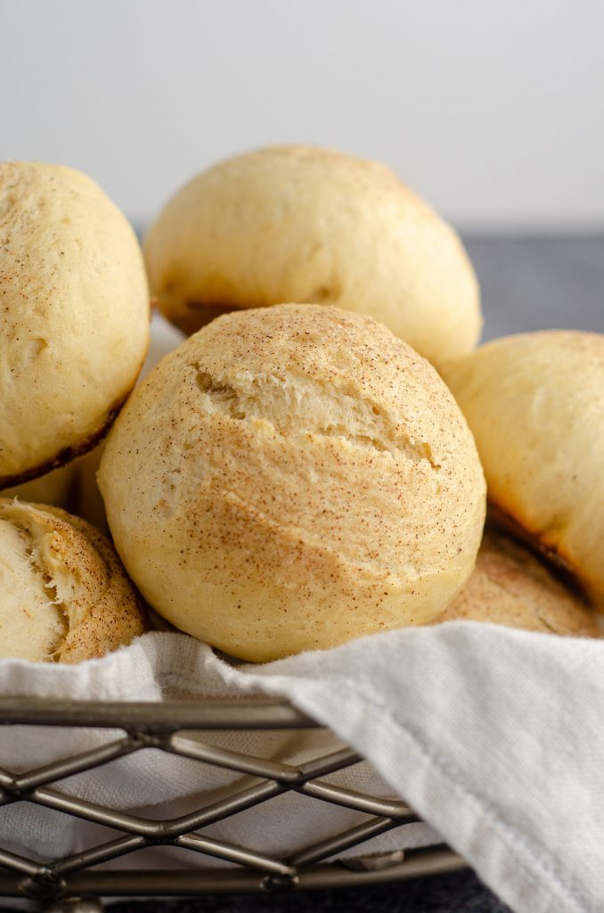 cardamom rolls sitting in a basket with a white kitchen cloth