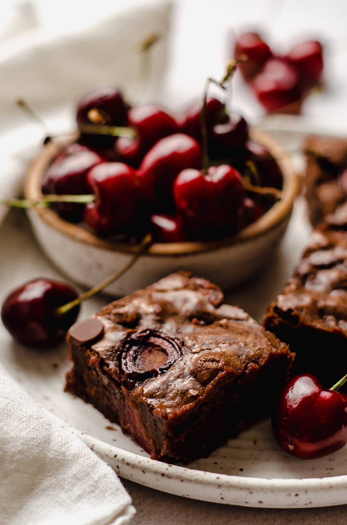 cherry brownies on a plate with a bowl of cherries