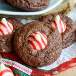 "Chocolate Peppermint Blossoms: A holiday take on the classic ""blossom"" cookie! A simple chocolate cookie speckled with chopped candy cane Hershey's Kisses and topped with a swirly whole one."