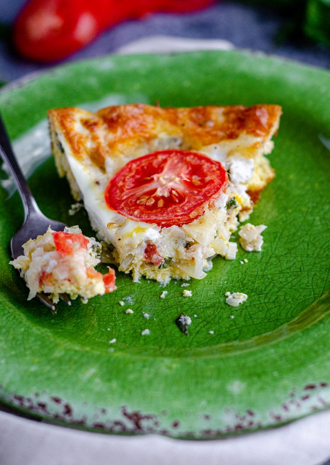 slice of crutless caprese quiche on a green plate with a fork and a bite taken out of it