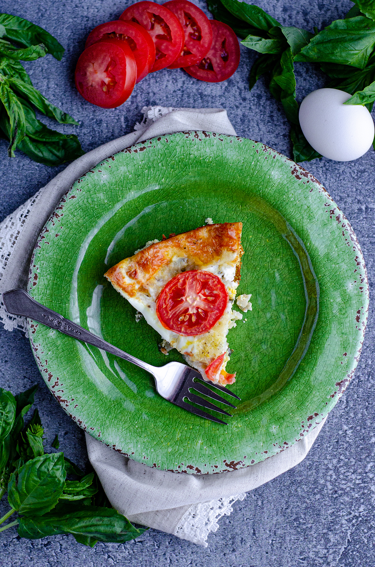 aerial photo of a slice of crustless caprese quiche on a green plate with a fork