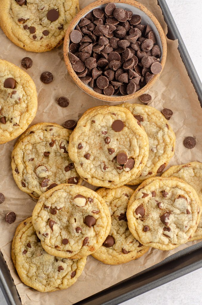 aerial photo of chocolate chip cookies on a baking sheet lined with parchment and a bowl of chocolate chips