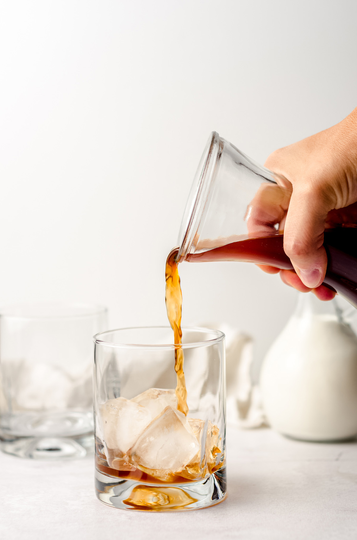 pouring cold brew coffee into a glass with ice