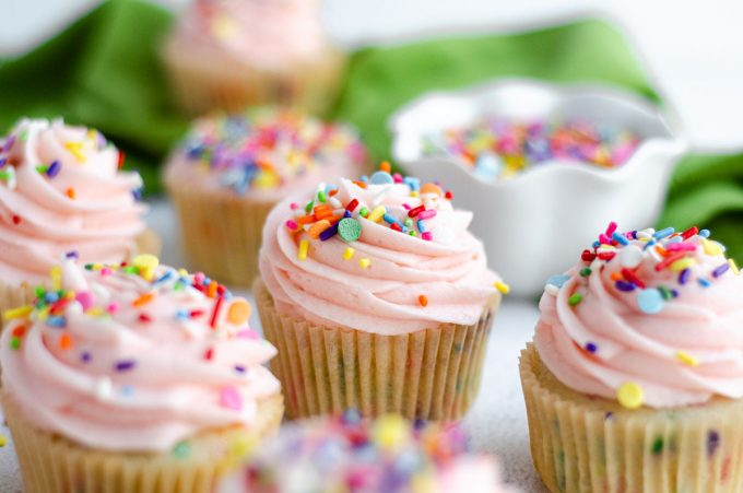 homemade funfetti cupcakes with pink frosting and a bowl of sprinkles in the background