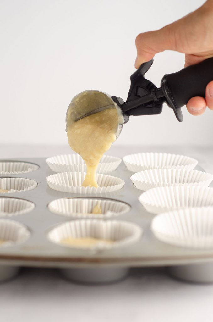 ice cream scooper putting vanilla bean cupcake batter into liners