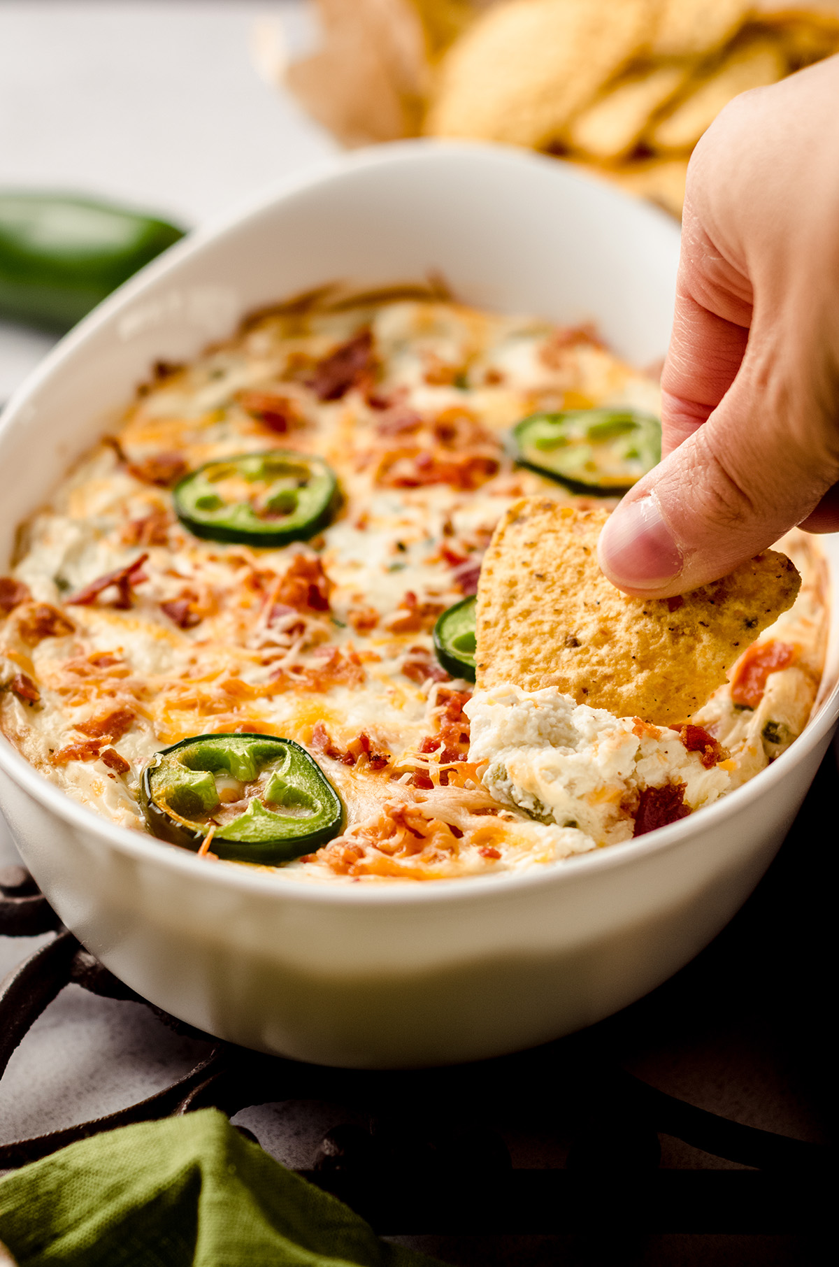 hand dipping a chip in to jalapeno cream cheese dip