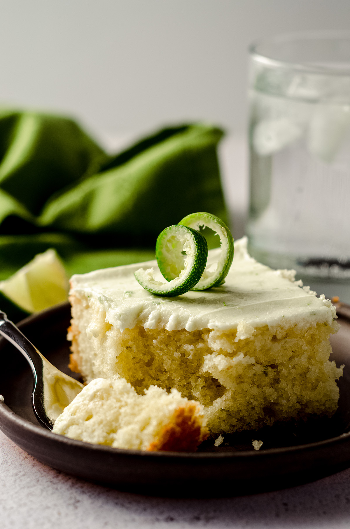 slice of gin and tonic cake sitting on a plate with a fork and a bite taken out of it